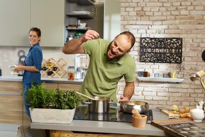Junge Paare, die zusammen in der Küche kochen lizenzfreie stockfotos