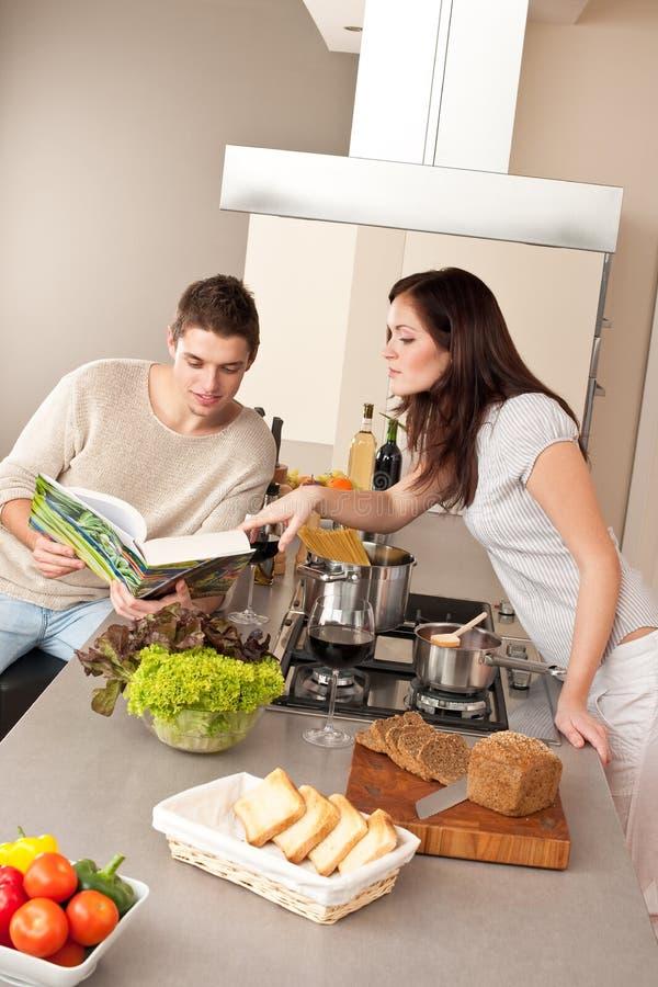 Junge Paare, die zusammen in der Küche kochen stockbild