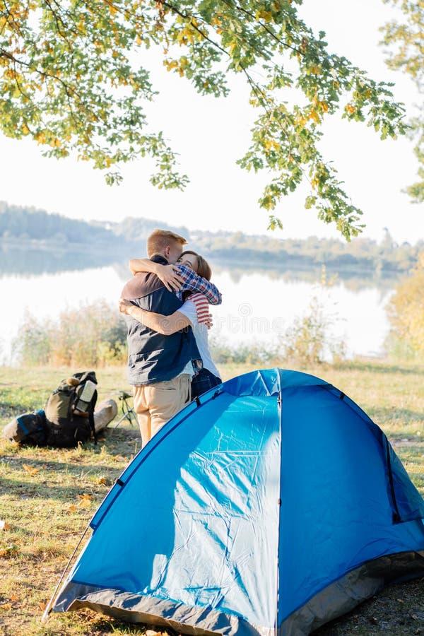 Junge Paare, die zusammen ein Zelt, umarmend am Schluss auf Wanderung am See werfen stockfoto