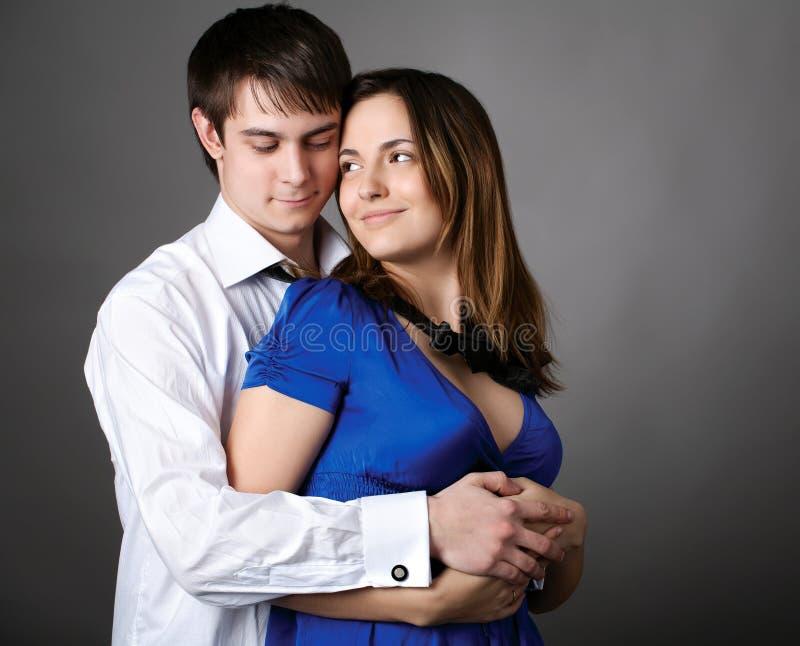 Junge Paare, die zusammen gegen eine graue Wand stehen stockfotos