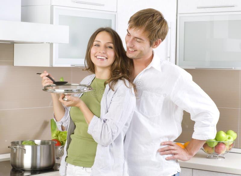 Junge Paare, die zusammen kochen stockbilder
