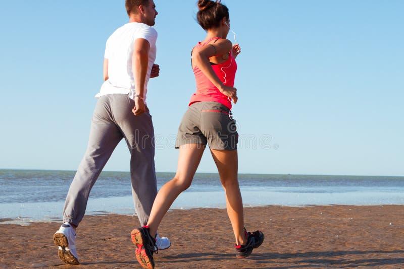 Junge Paare, die zusammen neben dem Wasser am Strand laufen Mann stockbilder