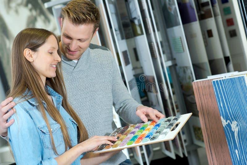 Junge Paare, die zwischen verschiedenen Glasfliesenmustern wählen lizenzfreie stockfotografie