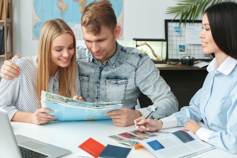 Junge Paare in einer Ausflugagenturkommunikation mit einem reisenden Konzept des Reisebüros, das Broschüre hält stockfotografie