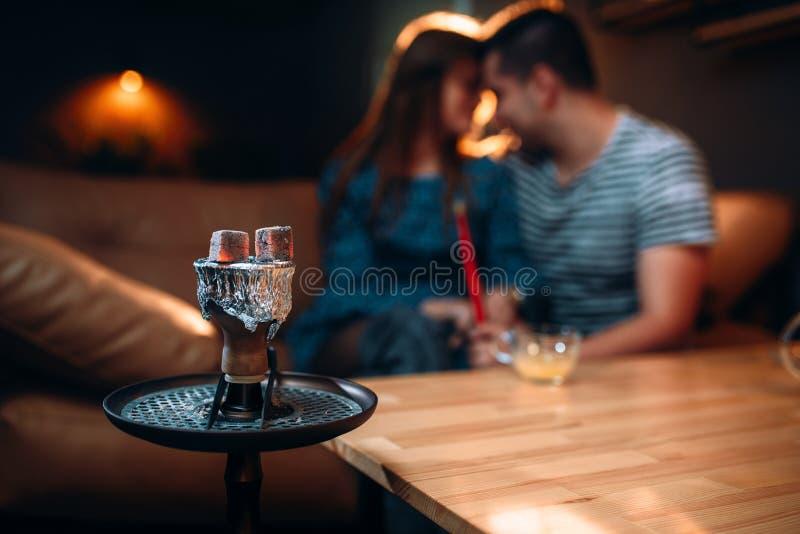 Junge Paare entspannen sich und rauchende Huka lizenzfreies stockfoto