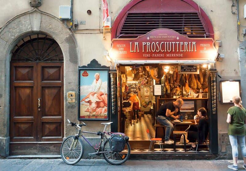 Junge Paare essen im Fleischrestaurant auf historischer Straße alter Toskana-Stadt zu Mittag stockfotografie