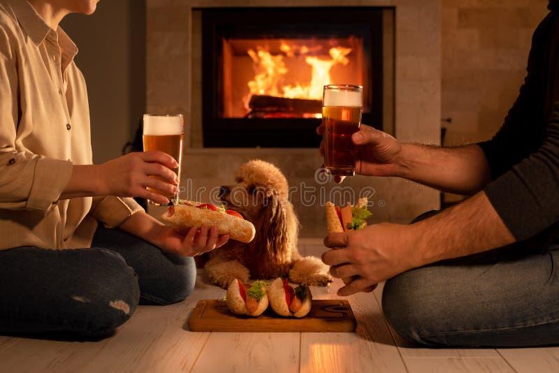 Junge Paare essen romantisches mit Grill grillten Würstchen und Bier zu Abend lizenzfreie stockfotografie