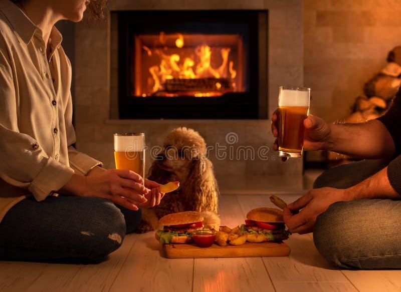 Junge Paare essen romantisches mit Hamburgern und Bier zu Abend stockfoto