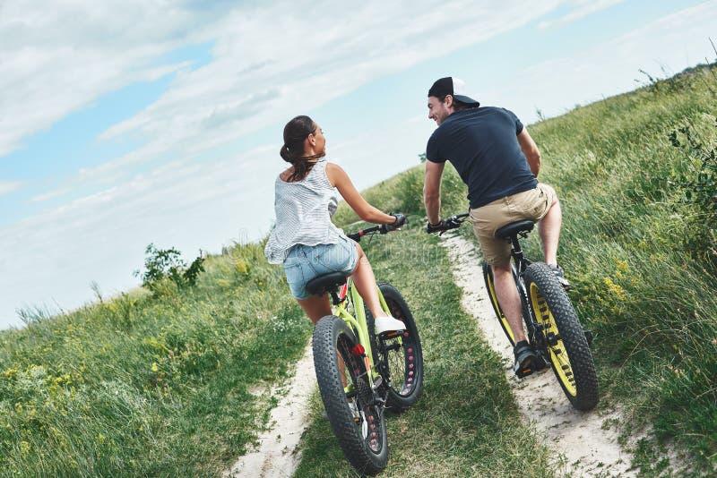 Junge Paare fahren an den grünen Hügeln rad Hintere Ansicht lizenzfreie stockbilder