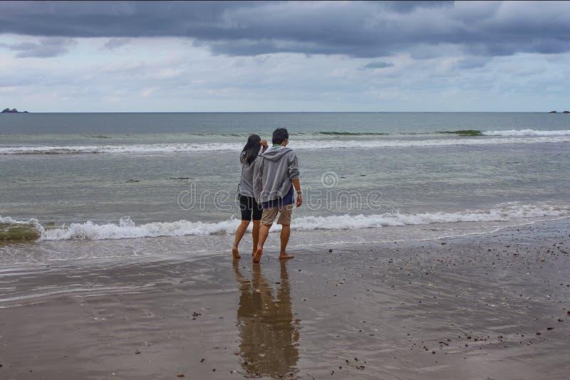 Junge Paare gehen entlang das nasse Strandhändchenhalten an einem stürmischen Tag in Bryron-Bucht NSW Australien 8 29 2014 stockfotografie