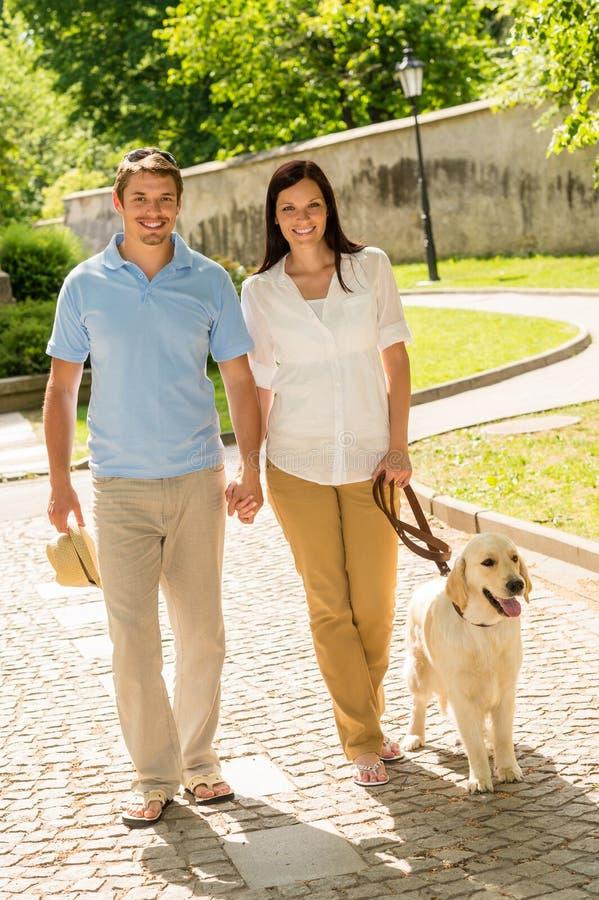 Junge Paare in gehendem Park der Liebe Hunde lizenzfreie stockfotografie