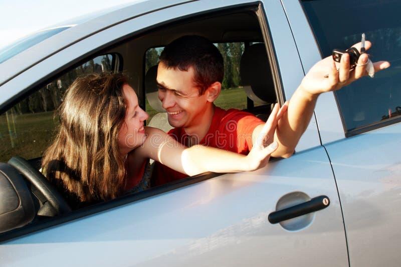 Junge Paare in gerade gekauftem Auto lizenzfreie stockfotografie