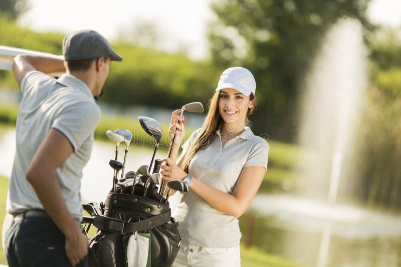 Junge Paare am Golfgericht lizenzfreie stockfotos