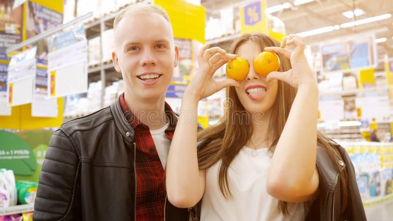 Junge Paare am Grossmarkt M?dchen macht lustige Grimasse mit den Tangerinen, die Kamera im Supermarkt betrachten stockfotos
