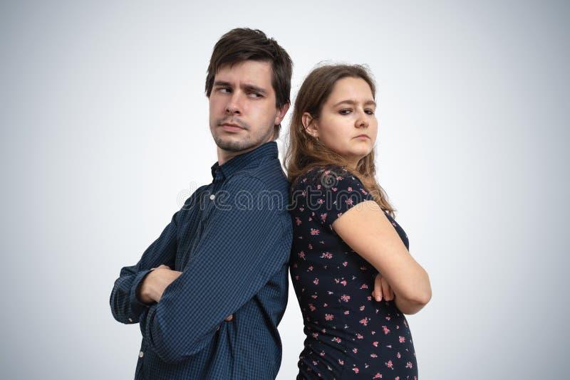 Junge Paare haben Probleme Umkippenmann- und -frauenstellung zurück zu Rückseite stockfotografie