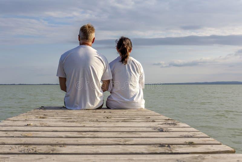 Junge Paare heraus auf dem hölzernen Pier lizenzfreie stockfotografie