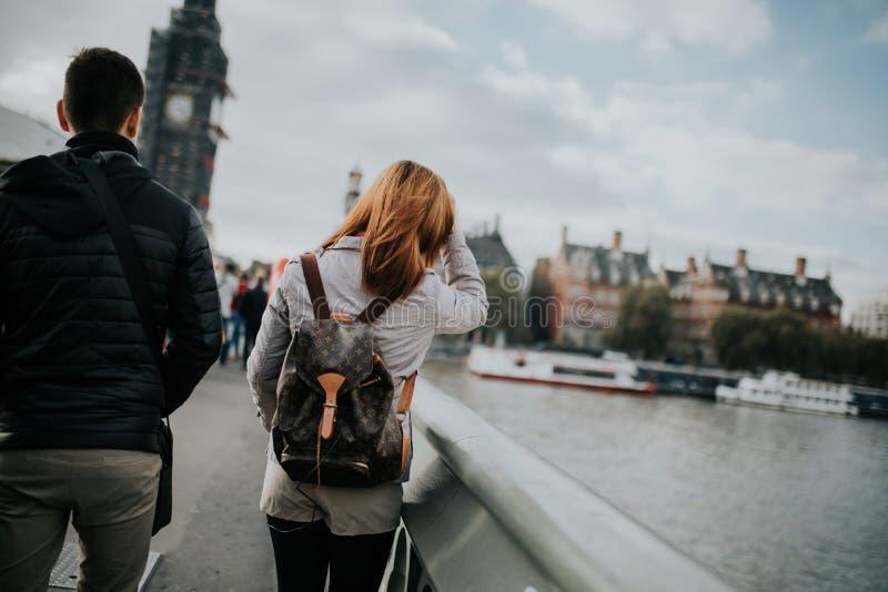 Junge Paare in ihren Rückseiten, gehend durch Westminster-Brücke, mit der Themse und Big Ben im Hintergrund, in London, England lizenzfreie stockbilder