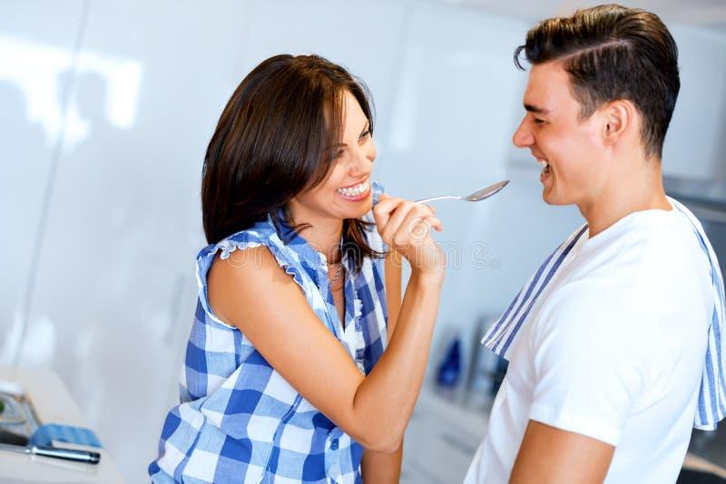 Junge Paare im Küchenprobierenlebensmittel lizenzfreie stockfotografie