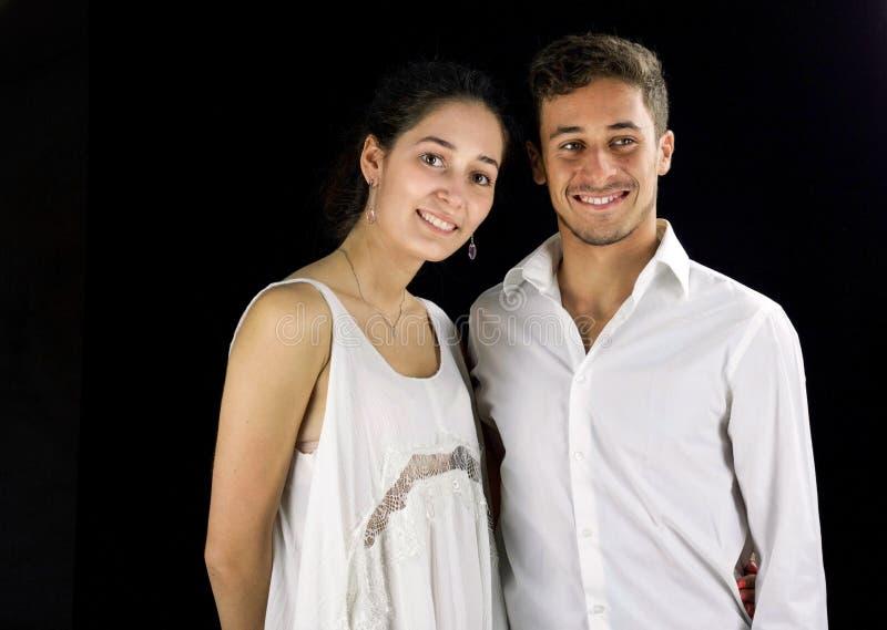 Junge Paare kleideten in weißem vorbereiten für eine Partei an lizenzfreies stockfoto