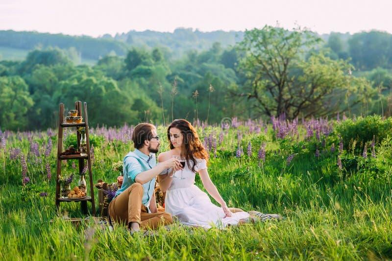 Junge Paare klirren Gläser mit Rotwein auf einem im Freien stockfotografie