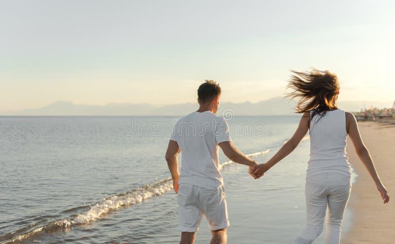 Junge Paare laufen gelassen weg auf dem Strand stockfotografie