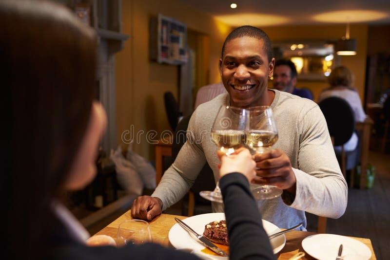 Junge Paare machen einen Toast am Restaurant, Überschulteransicht lizenzfreie stockfotografie