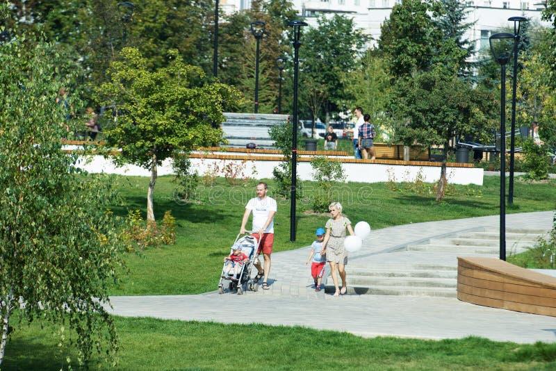 Junge Paare mit dem Kinderspazierg?nger, der in Butovo-Park, Moskau, Russland geht lizenzfreies stockbild