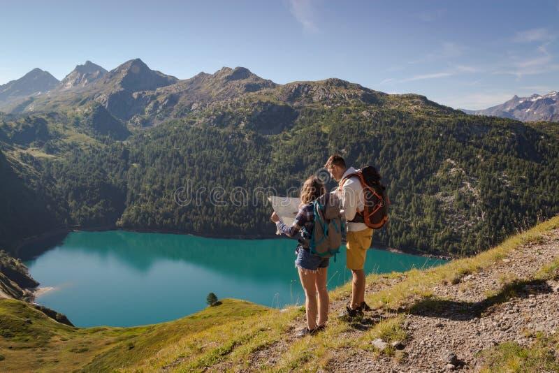 Junge Paare mit dem Rucksack, der eine Karte in den Schweizer Alpen liest See ritom als Hintergrund lizenzfreie stockfotos