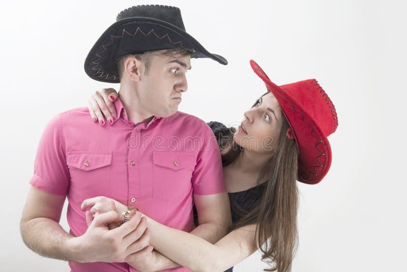 Junge Paare mit den Cowboyhüten, die dumme Gesichter auf Weiß machen lizenzfreies stockbild