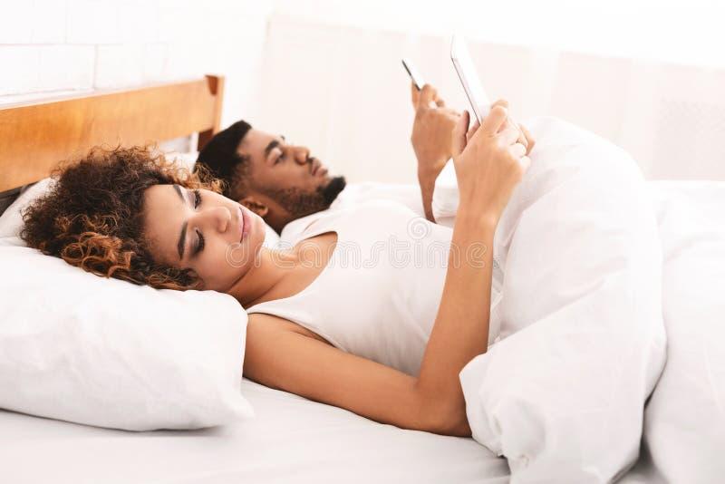 Junge Paare mit den Handys, die vom Bett arbeiten stockbilder