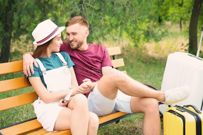 Junge Paare mit den Koffern, die auf Bank sitzen stockfoto