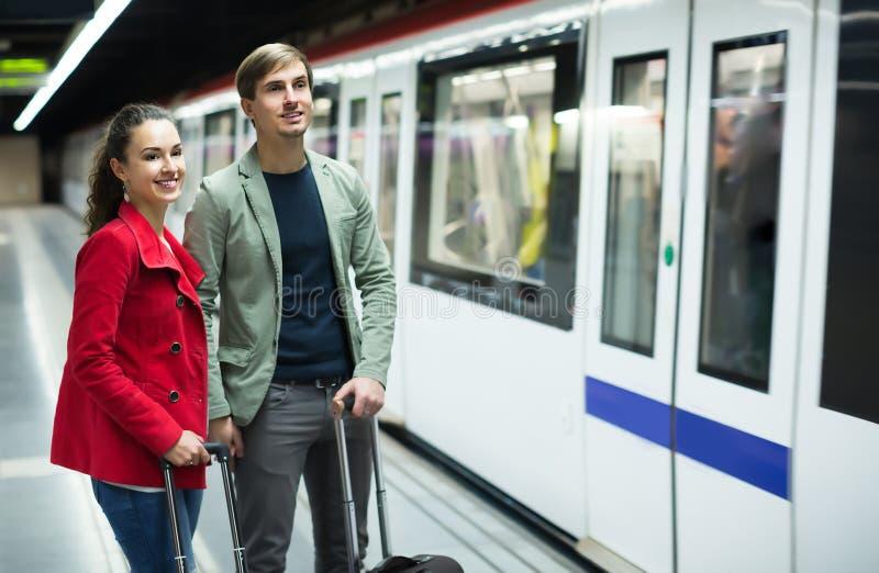 Junge Paare mit den Koffern, die auf Zug warten lizenzfreie stockfotografie