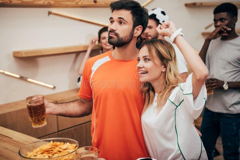 junge Paare mit den multikulturellen Freunden, die Fußballspiel feiern und aufpassen stockfotos