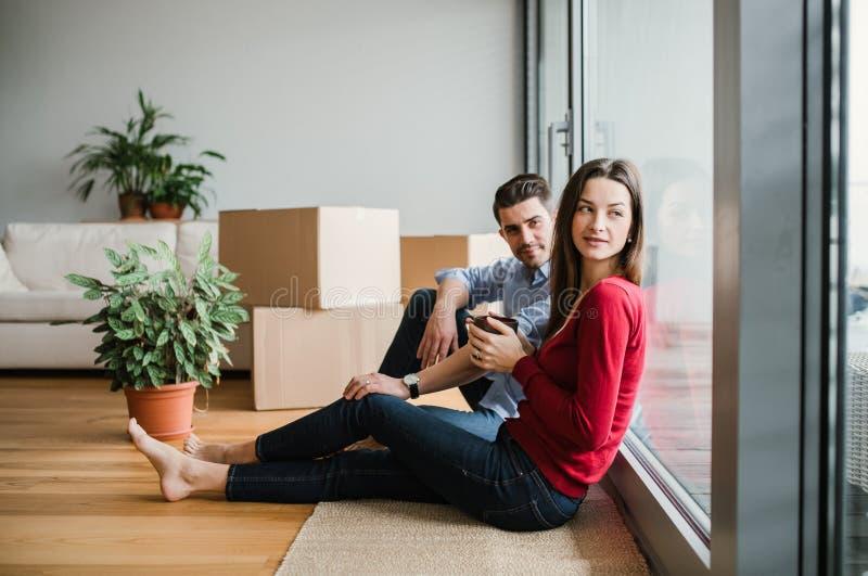Junge Paare mit den Pappschachteln, die in ein neues Haus, sitzend auf einem Boden sich bewegen lizenzfreie stockfotografie