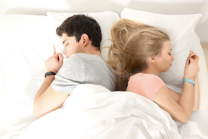 Junge Paare mit den Schlafverfolgern, die im Bett stillstehen lizenzfreies stockbild