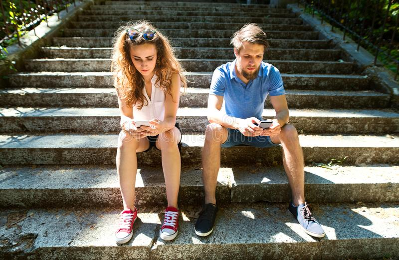 Junge Paare mit den Smartphones, die auf Treppe in der Stadt sitzen lizenzfreie stockbilder