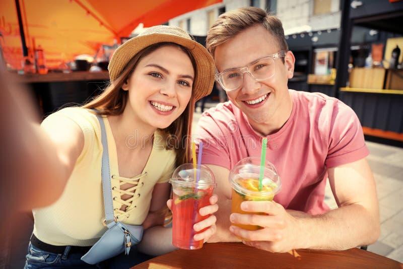 Junge Paare mit den Sommergetränken, die selfie nehmen stockfotografie
