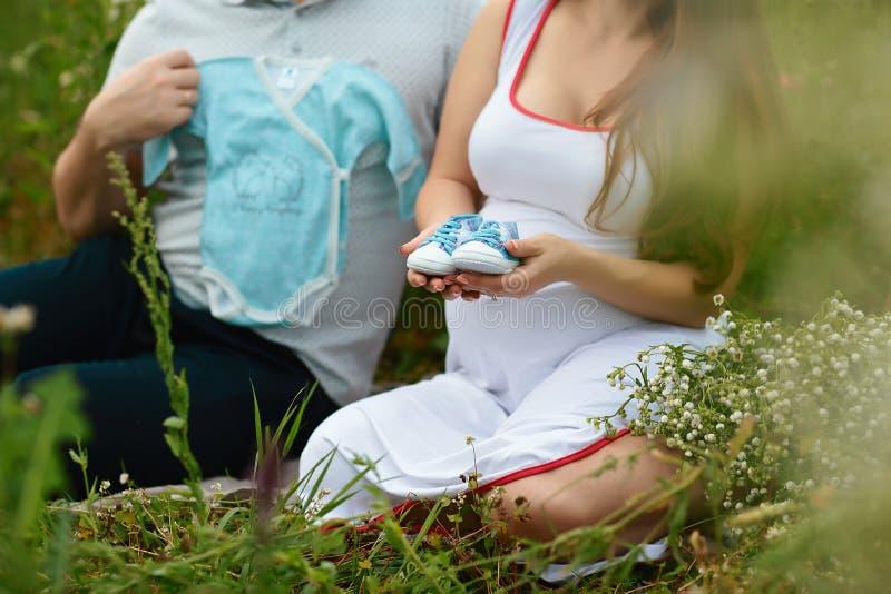 Junge Paare mit der schwangeren Frau, welche zusammen die Geschenkkinderkleidung und Säuglingsschuhe - glückliche Menschen bereit stockfotos
