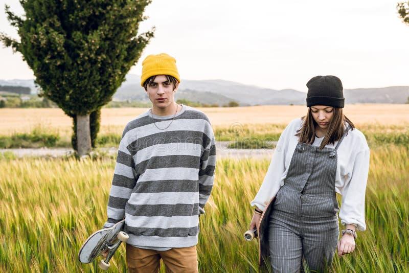 Junge Paare mit der zufälligen Art, die ein Skateboard reitet Tausendjähriger junger Lebensstil lizenzfreie stockfotografie