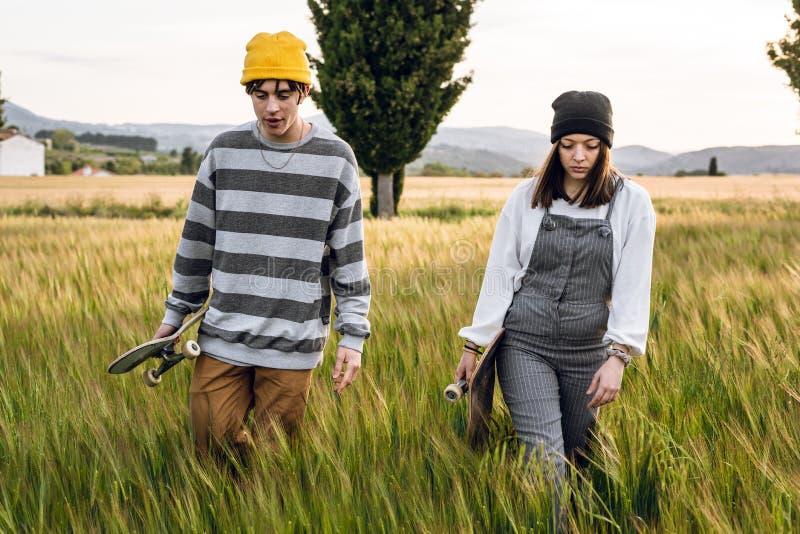 Junge Paare mit der zufälligen Art, die ein Skateboard reitet Tausendjähriger junger Lebensstil stockfotos
