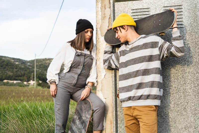 Junge Paare mit der zufälligen Art, die ein Skateboard reitet Tausendjähriger junger Lebensstil stockbild