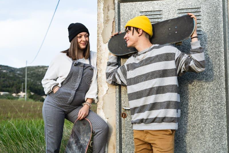 Junge Paare mit der zufälligen Art, die ein Skateboard reitet Tausendjähriger junger Lebensstil stockfoto