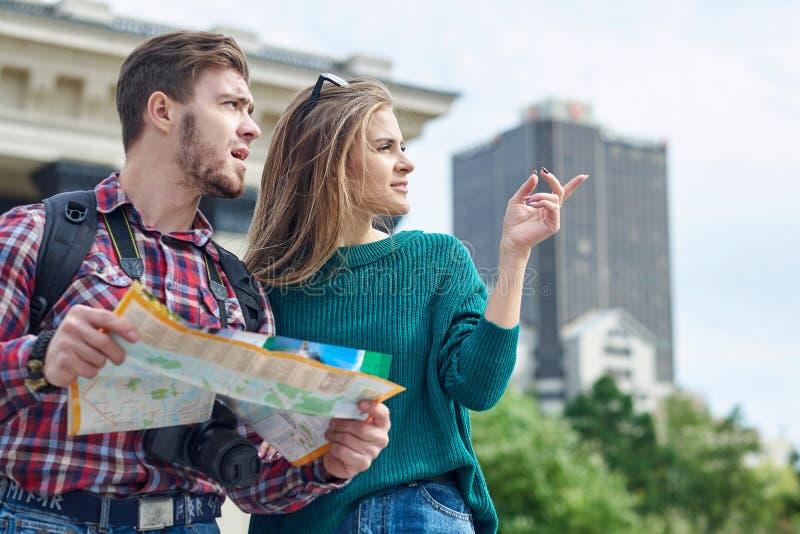 Junge Paare mit einer Karte in der Stadt Besichtigungsstadt der glücklichen Touristen mit Karte lizenzfreie stockfotografie