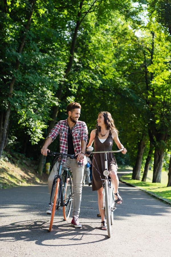 Junge Paare mit Fahrrädern stockfotos