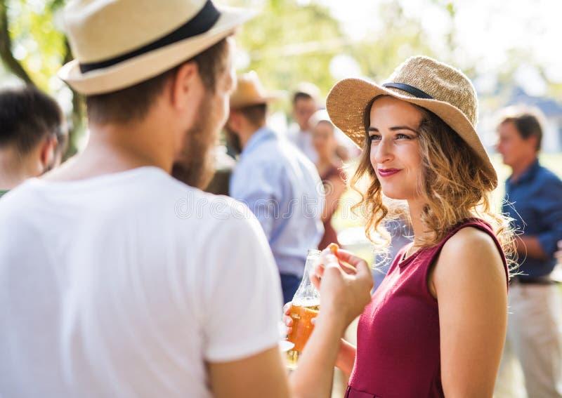 Junge Paare mit Familie auf einer Feier oder einer Grillpartei draußen im Hinterhof lizenzfreies stockbild