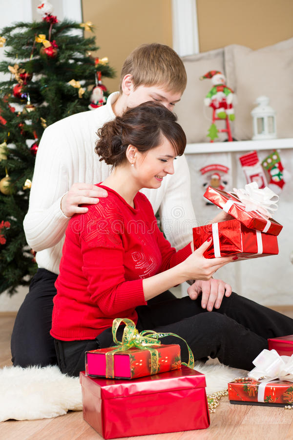 Junge Paare mit Geschenk vor Weihnachtsbaum lizenzfreie stockfotos