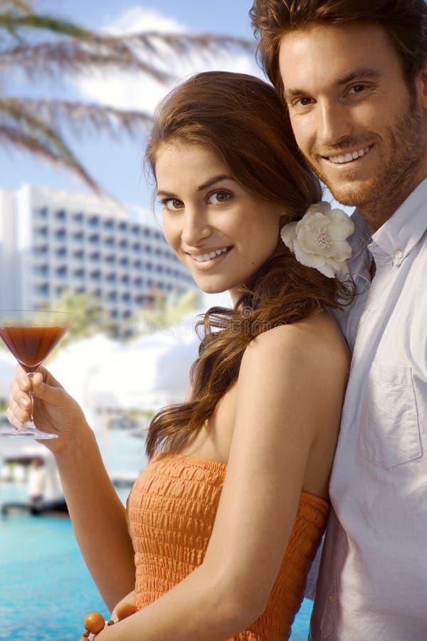 Junge Paare mit Getränk am Luxusstrandurlaubsort lizenzfreie stockfotografie