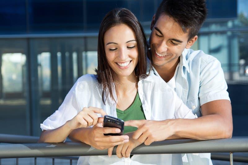 Junge Paare mit intelligentem Telefon lizenzfreies stockfoto
