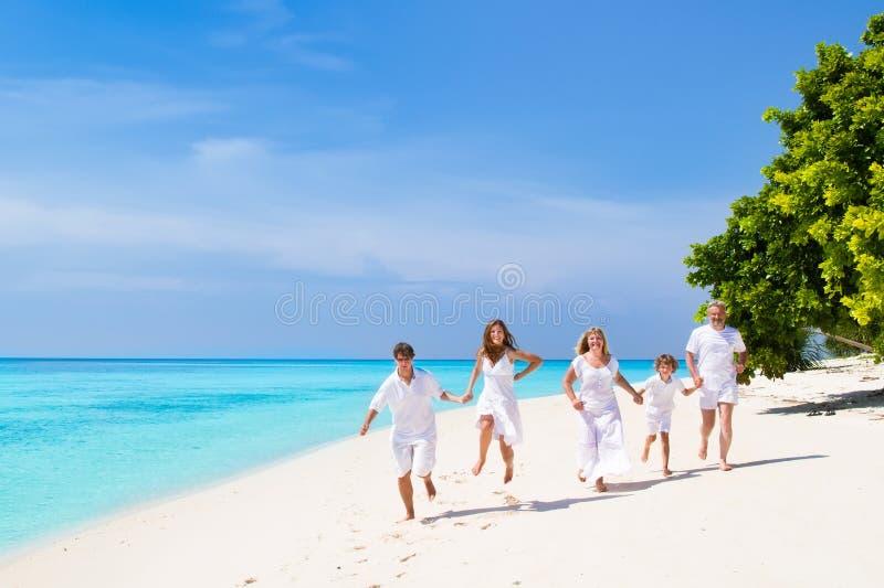 Junge Paare mit Kind und Großeltern auf Strand lizenzfreie stockbilder