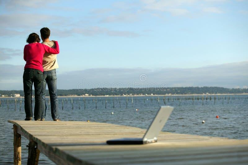 Junge Paare mit Laptop-Computer auf einem Dock lizenzfreies stockfoto